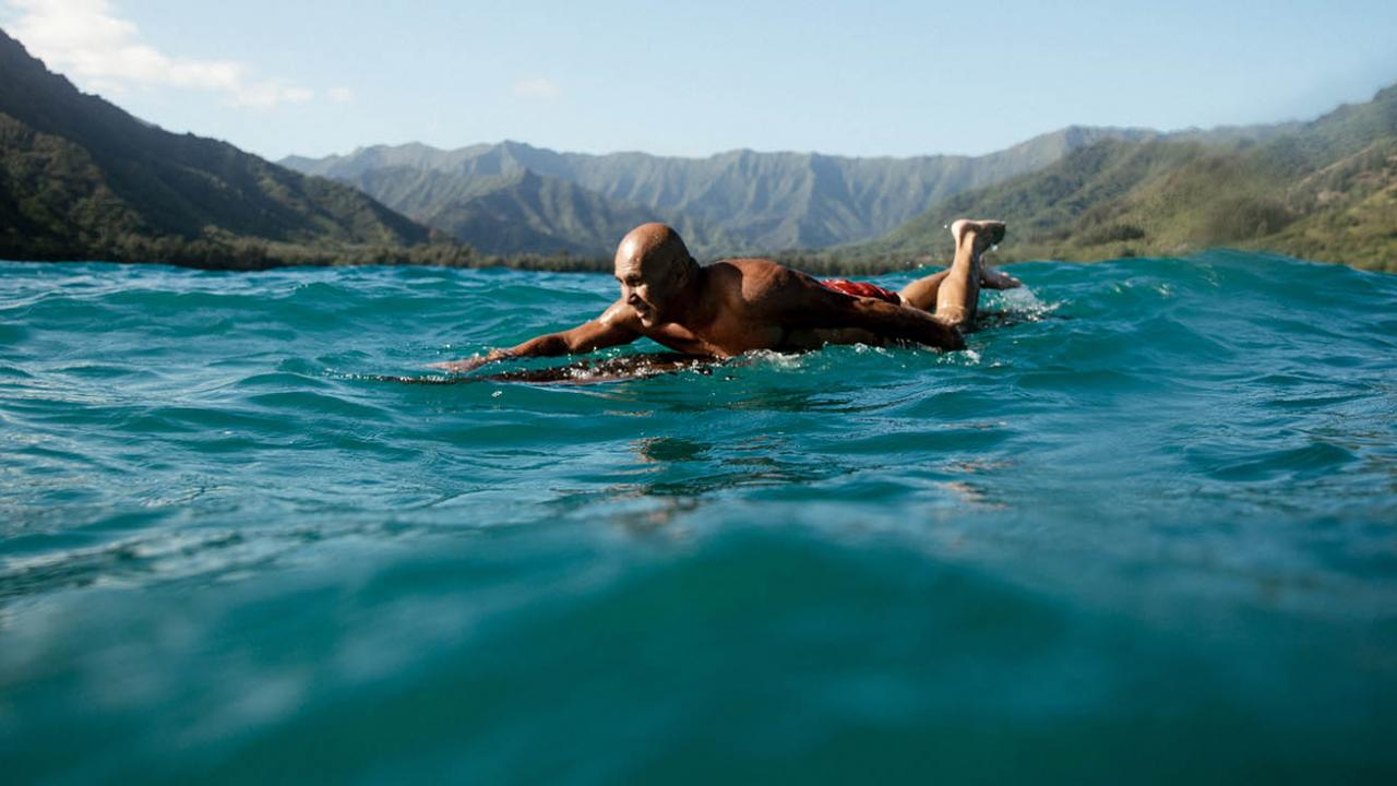 surfer on board in ocean with mountain background Oahu