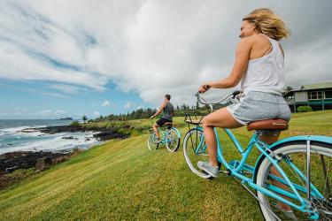 Couple riding bikes by the beach